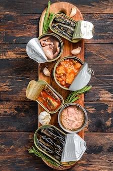 Otwarte puszki konserwują z saury, łososiem, szprotkami, sardynkami, kalmarem i tuńczykiem. ciemne tło drewniane. widok z góry.