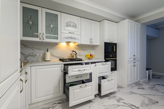 Otwarte szuflady z naczyniami w nowoczesnej, białej kuchni w klasycznym stylu