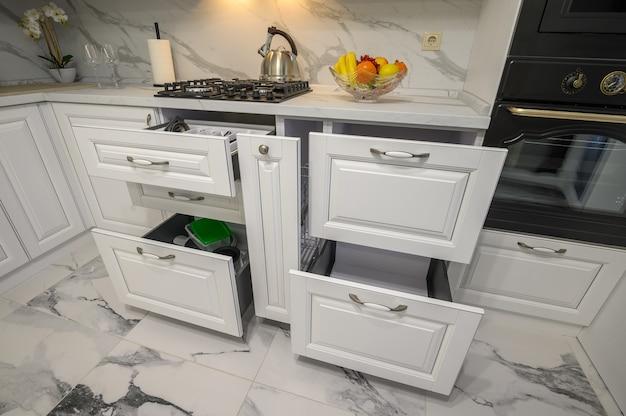 Otwarte szuflady z naczyniami w nowoczesnej białej kuchni