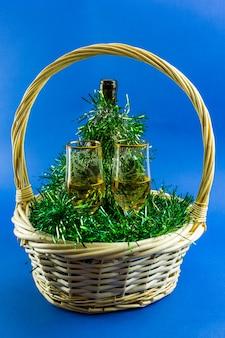 Otwarte wino z napełnionymi kieliszkami w koszu ozdobionym zielonym blichtrem. dekoracja świąteczna i noworoczna.