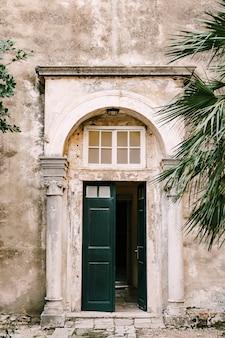 Otwarte zielone drzwi ze szkłem do budynku z kolumnami i łukiem