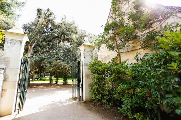 Otwarto starą metalową bramę na dziedziniec. kamienny mur wokół bramy