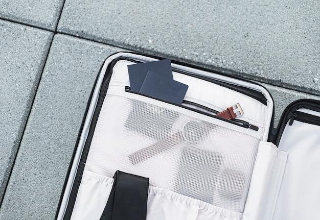 Otwarty bagaż siedzi na betonie