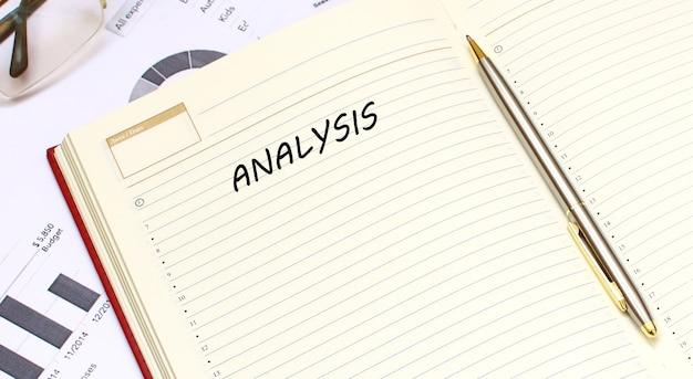Otwarty dziennik z tekstem leży na biurku z wykresami finansowymi. pomysł na biznes.