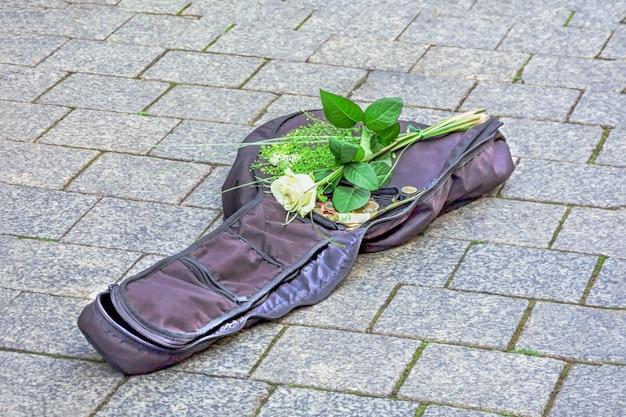 Otwarty futerał na skrzypce, pieniądze i piękna biała róża na chodniku