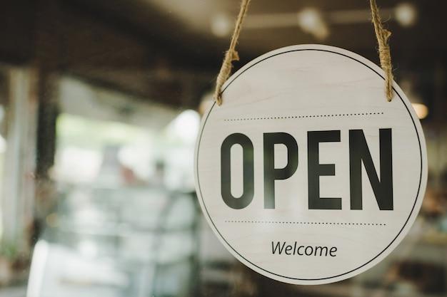 Otwarty. kawiarnia kawiarnia tekst na tabliczce z napisem vintage wisi na szklanych drzwiach w nowoczesnej kawiarni kawiarnia, restauracja kawiarni, sklep detaliczny, właściciel małej firmy, jedzenie na wynos, jedzenie i picie