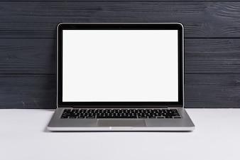 Otwarty laptop z pustym białym ekranem na białym biurku przeciw czarnemu drewnianemu tłu