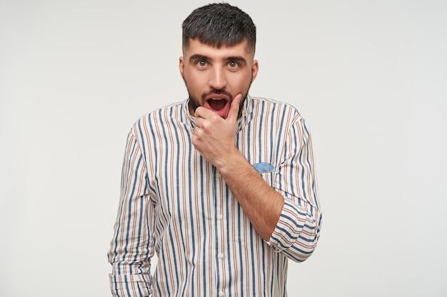 Otwarty, młody, piękny, krótkowłosy brunet z brodą trzymający brodę z podniesioną ręką, patrząc zdumiewająco z otwartymi ustami, odizolowany na białej ścianie