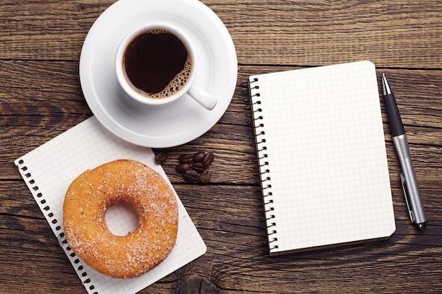 Otwarty notatnik i filiżanka kawy z pączkiem