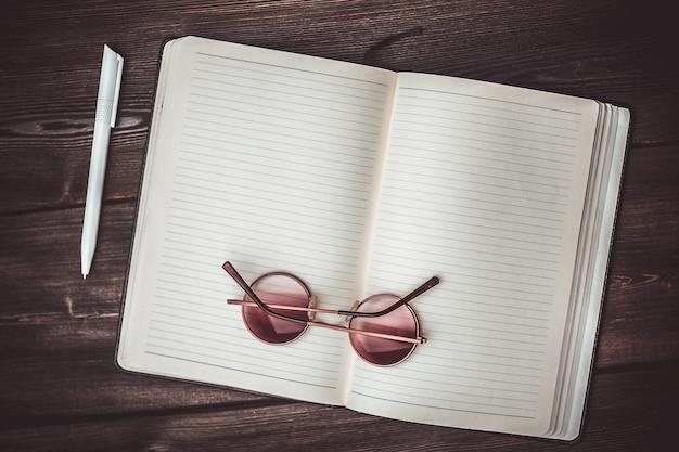 Otwarty notatnik leży na drewnianym stole i telefon komórkowy z okularami długopis