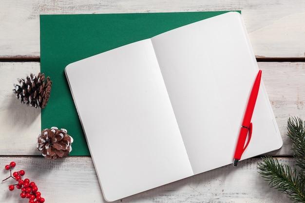 Otwarty notatnik na drewnianym stole z długopisem i ozdóbkami świątecznymi.