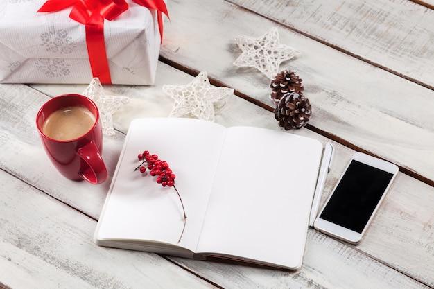 Otwarty notatnik na drewnianym stole z telefonem i świątecznymi ozdobami.