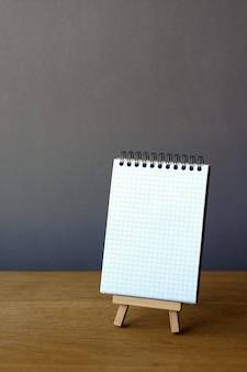 Otwarty notatnik na miniaturowej sztalugach na drewnianej powierzchni
