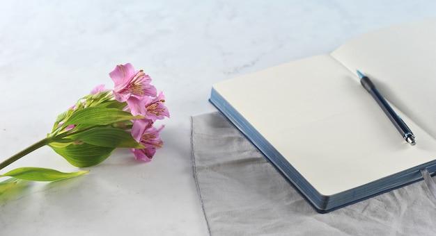 Otwarty notatnik z kwiatami na białym marmurze