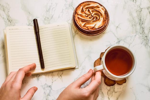 Otwarty notatnik z pustym obszarem, długopisem i filiżanką czarnej herbaty na białym marmurowym stole w godzinach porannych.