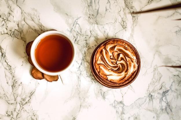Otwarty notatnik z pustym obszarem, piórem i filiżanką czarna herbata na bielu