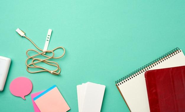 Otwarty notatnik z pustymi białymi kartkami, bezprzewodowymi słuchawkami i ładowarką