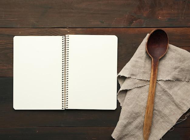 Otwarty notatnik z pustymi białymi prześcieradłami i naczyniami kuchennymi