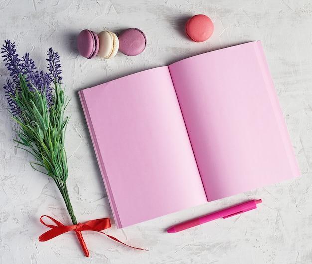 Otwarty notatnik z pustymi różowymi stronami, czerwony długopis