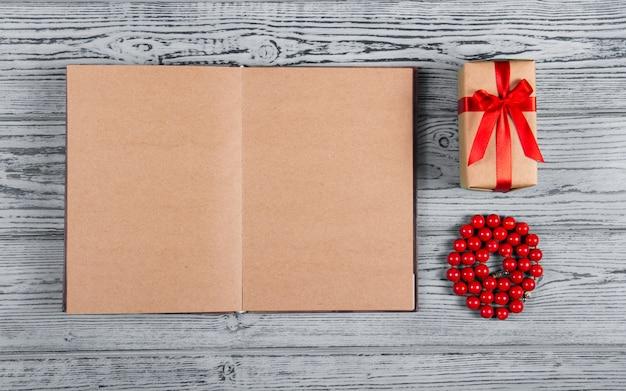Otwarty notatnik z pustymi stronami, koralikami z czerwonego korala i pudełkiem prezentowym