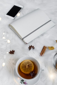 Otwarty notatnik z smartphone w pobliżu filiżanki herbaty