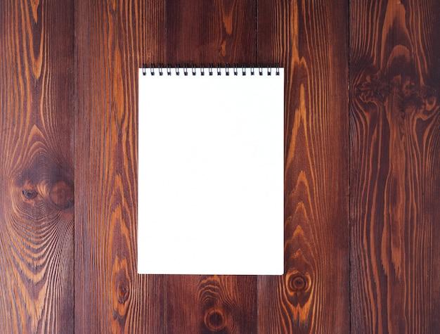 Otwarty notepad z spiralą na ciemnego brązu drewnianym stole, odgórny widok