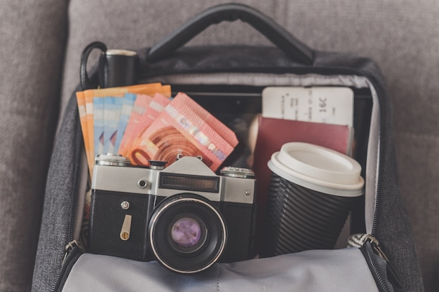 Otwarty plecak z rzeczami potrzebnymi na podróż, aparat, pieniądze, paszport i bilety