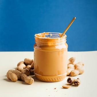 Otwarty słoik masła orzechowego z łyżeczką i orzeszkami ziemnymi w skorupce na kolorowej ścianie. szybkie śniadanie, jedzenie dla wegetarian.