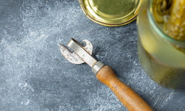 Otwarty słoik ogórków i otwieracz do słoików na szarym stole.