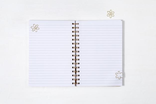 Otwarty szkolny notatnik na wiosnę z czystą podszewką i złotymi metalowymi klipsami na białym biurku. powrót do koncepcji szkoły. widok z góry.