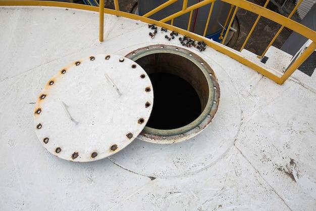 Otwarty zardzewiały właz na zbiorniku paliwa stały stożek na dachu zbiornika magazynowego o ograniczonej przestrzeni