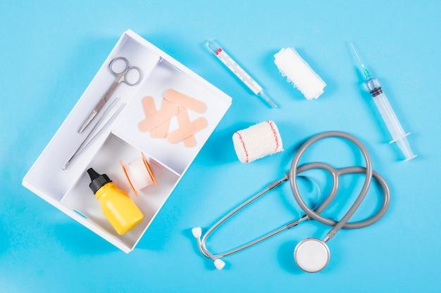 Otwarty zestaw pierwszej pomocy z wyposażeniem medycznym na niebieskim tle