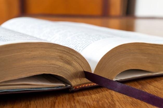 Otwiera książkową świętą biblię na żółtym drewnianym tle