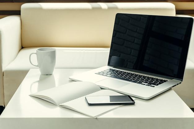 Otwiera laptop na stołowej pobliskiej kanapie, domowy wnętrze. koncepcja pracy freelancer
