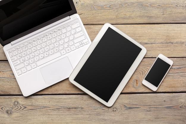Otwiera laptop z cyfrową pastylką i białym smartphone zakończeniem w górę odgórnego widoku