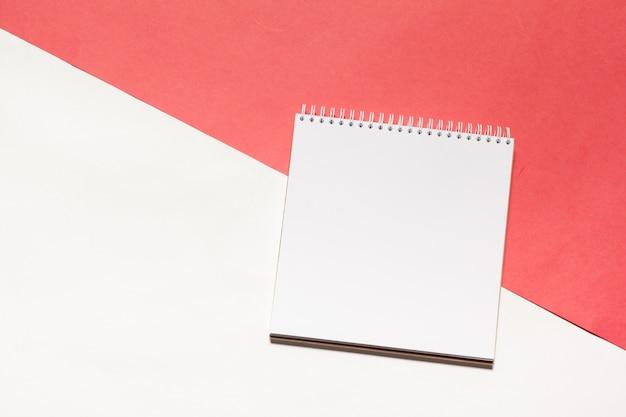 Otwiera pustego notatnika na kolorowym tle