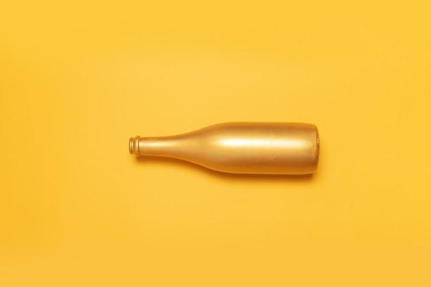 Otwiera złotą szampańską butelkę na żółtym tle