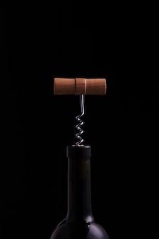 Otwieranie butelki wina z korkociągiem na czarnym tle