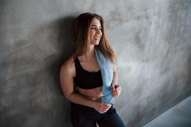 Otwieranie butelki wodą. zdjęcie pięknej blondynki na siłowni w czasie weekendu