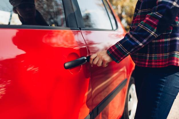Otwieranie drzwi samochodu. kobieta otwiera czerwony samochód kluczem