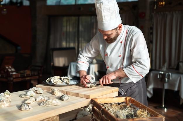 Otwieranie pustych i płaskich ostryg. szef kuchni otwiera ostrygi w restauracji.
