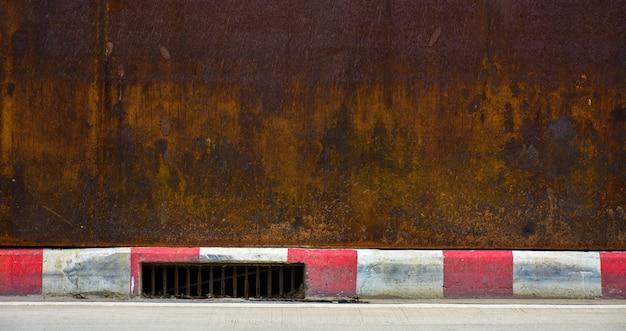 Otwór drenażowy przy krawężniku czerwono-białego chodnika - droga w mieście