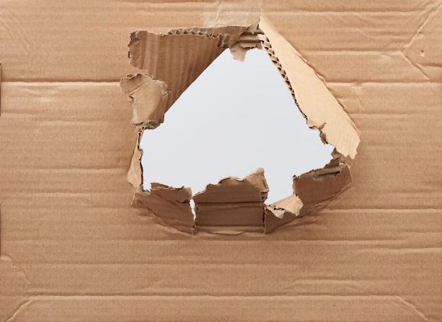 Otwór w brązowym papierze kartonowym z poszarpanymi i zakrzywionymi krawędziami