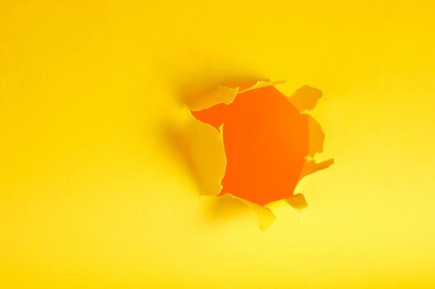 Otwór z rozdartego żółtego papieru. skopiuj miejsce