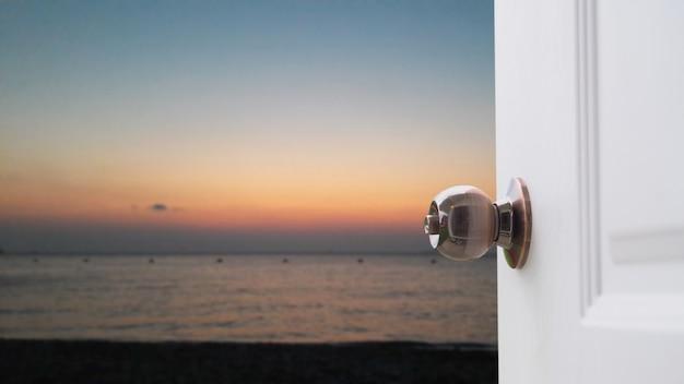 Otwórz białe drzwi nad morzem.