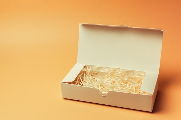 Otwórz białe pudełko na prezent w środku z papierowym sianem