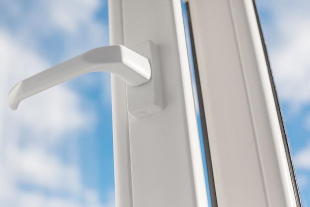 Otwórz biały plastikowy uchwyt do okna