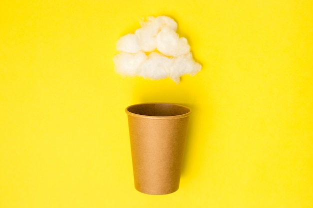 Otwórz craft papierowy kubek z chmurą waty na żółtym tle. leżał płasko. koncepcja kreatywnych minimalne jedzenie.