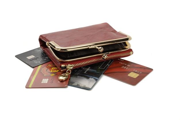 Otwórz czerwoną torebkę leżącą na kartach kredytowych, na białym tle