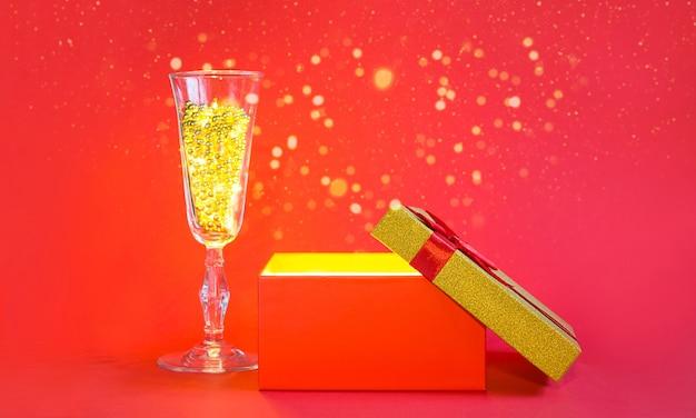 Otwórz czerwone pudełko ze złotym blaskiem i brokatem w środku oraz kieliszek do szampana z koralikami bąbelkowymi, baner, copyspace